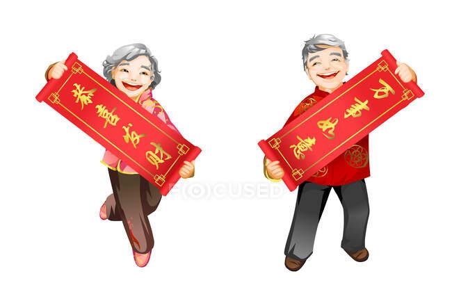 Senior couple holding Chinese New Year couplets — Stock Photo