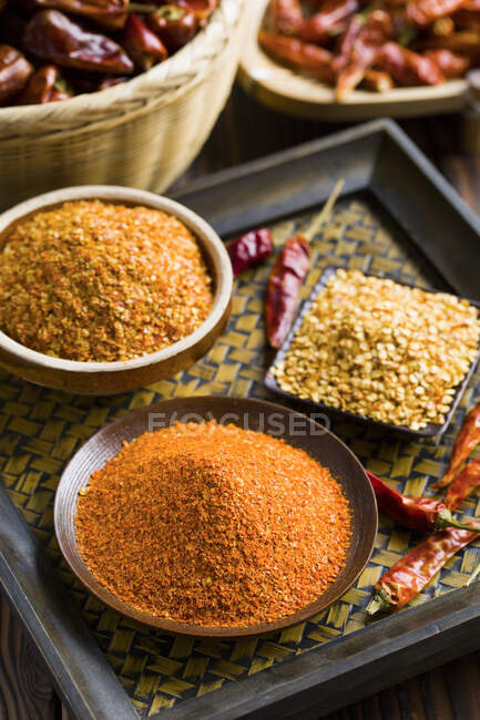 Chili pepper spices in bowls with dried peppers — Stock Photo