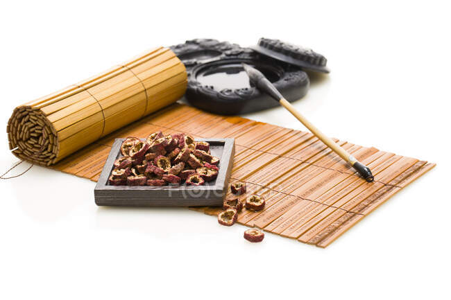 Inkstone and writing brush, hawthorn berries on bamboo mat — Stock Photo