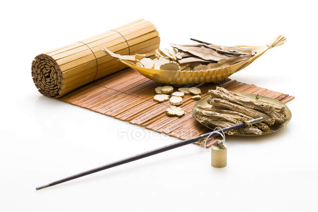 Traditional chinese medicine herbs and incense stick on bamboo mat — Stock Photo