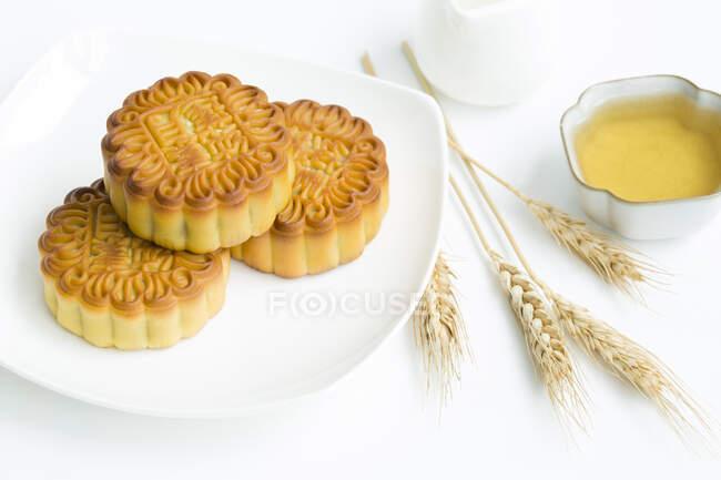 Torte di luna e tè con spikelets sul tavolo bianco — Foto stock