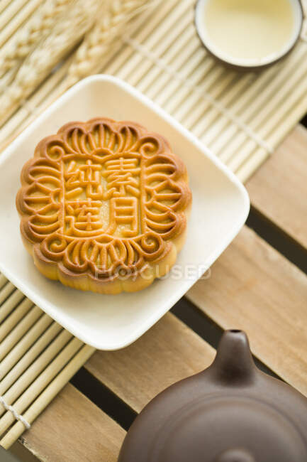 Mooncake, teapot and tea in cup on table — Stock Photo