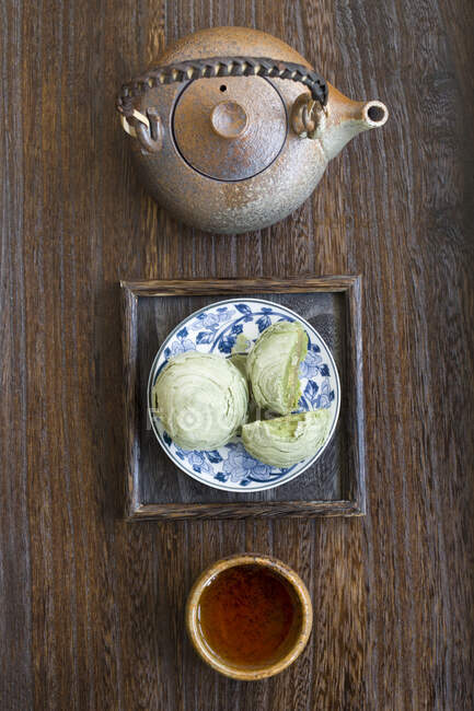 Matcha crisp desserts and tea in pot and cup — Stock Photo