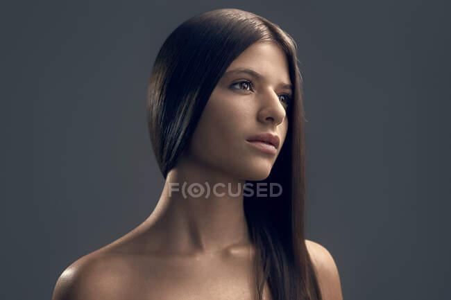 Ritratto ravvicinato di una bella giovane donna dai capelli lunghi che guarda da parte, fotografata in studio con luce cinematografica. Giovane donna latinoamericana con pelle perfetta. — Foto stock