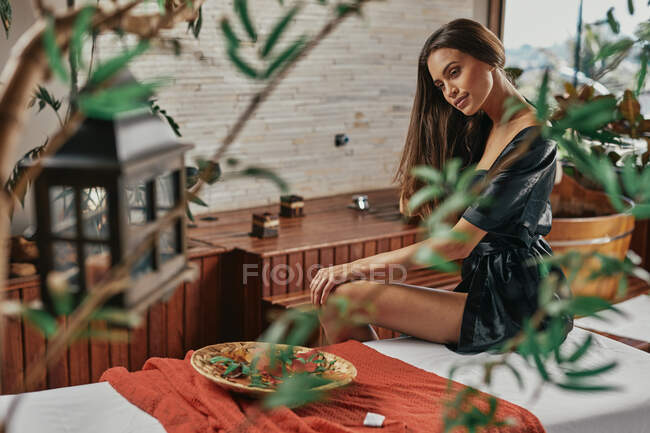 Beautiful smiling young tanned Latin American woman sitting and relaxing in spa — Stock Photo