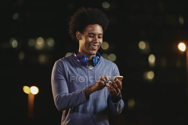 Elegante jovem homem de cabelos pretos andando em cena noturna urbana com fones de ouvido e telefone celular nas mãos — Fotografia de Stock