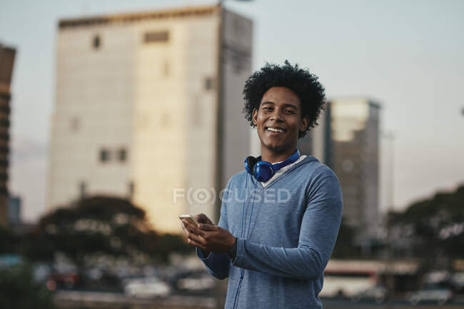 Stylish black haired man walking in urban scene with headphones and cell phone in hands. Young Brazilian man with black hair using smartphone on street. — Stock Photo