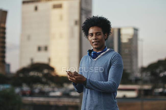 Homem de cabelos pretos elegante andando em cena urbana com fones de ouvido e telefone celular nas mãos. Jovem brasileiro com cabelo preto usando smartphone na rua. — Fotografia de Stock
