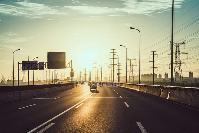 Traffic on highway at sunrise — Stock Photo