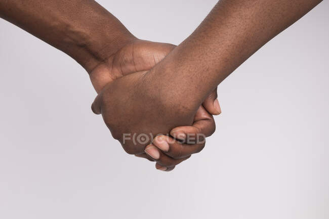 Cropped image of black woman and man holding hands — стокове фото