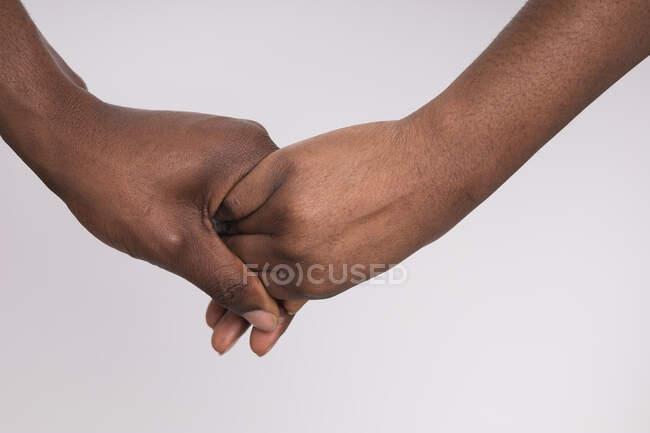 Abgeschnittenes Bild von schwarzer Frau und Mann beim Händchenhalten — Stockfoto