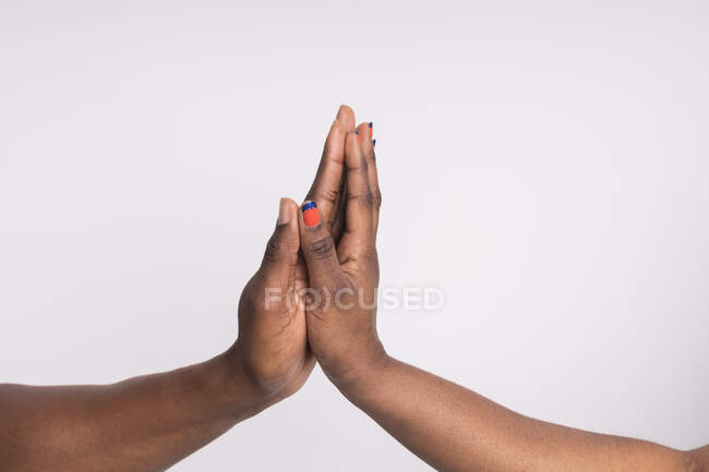 Cropped image of black woman and man touching with hands — Stock Photo