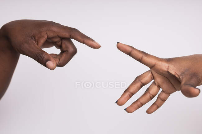 Cropped image of black woman and man reaching with hands — Stock Photo