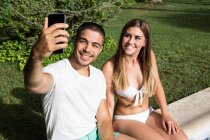 Young couple taking selfie at poolside — Stock Photo