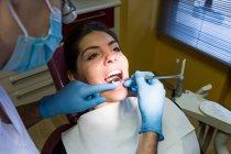 Dentiste, fournissant l'examen des dents pour femme — Photo de stock