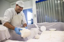 Man working with fresh cheese materials — Stock Photo