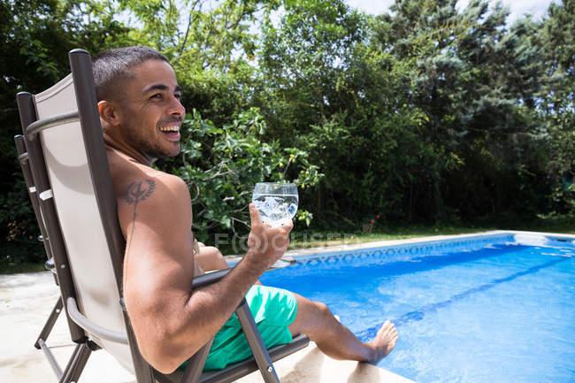 Jovem, descansando à beira da piscina — Fotografia de Stock