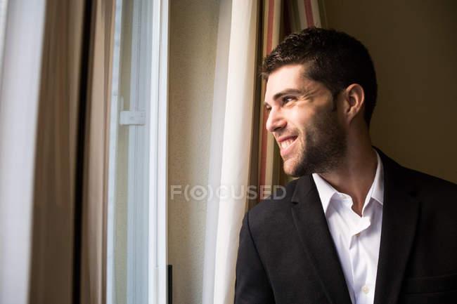 Businessman looking in window — Stock Photo