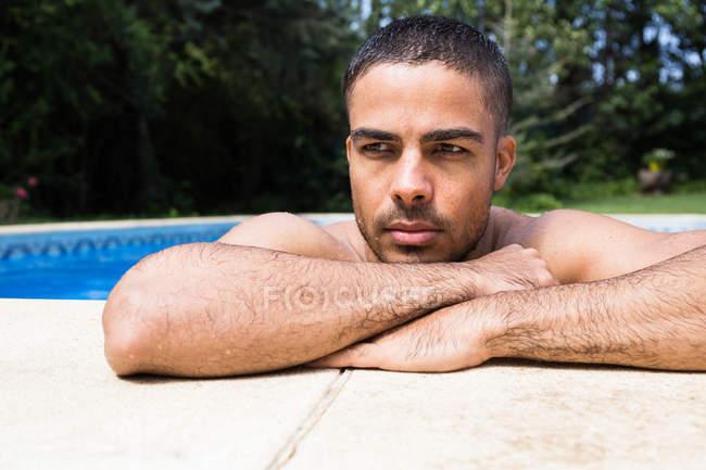 Jovem, descansando na piscina — Fotografia de Stock