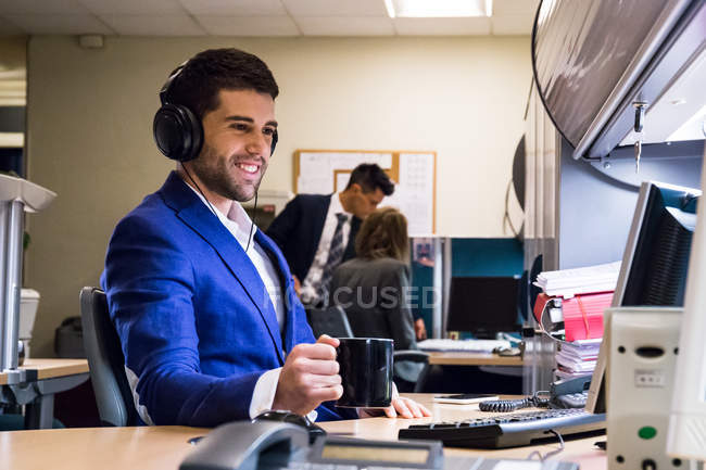 Office employee working on computer with coffee — Stock Photo