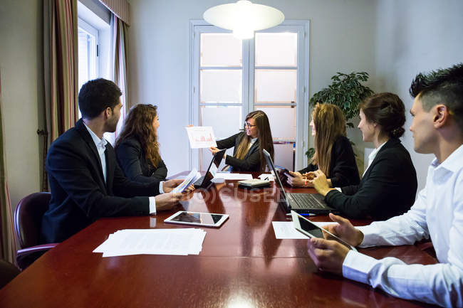 Businesswoman showing diagram to colleagues — Stock Photo