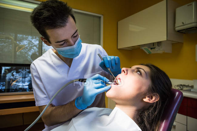 Dentist making oral procedure with drill — Stock Photo