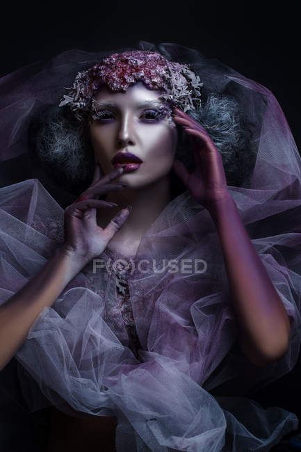 Portrait of woman with fantasy makeup touching her face — Stock Photo