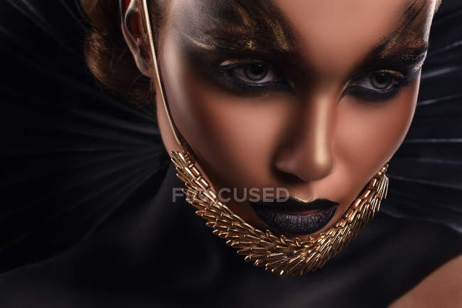 Portrait of woman with fantasy makeup and accessory on chin — Stock Photo