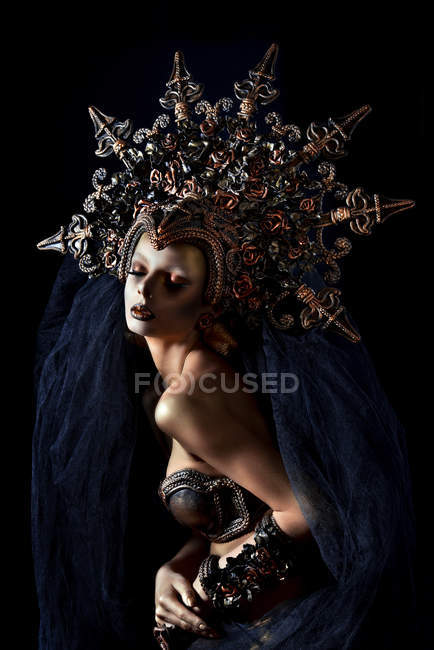 Portrait of woman with fantasy makeup in large crown — Stock Photo