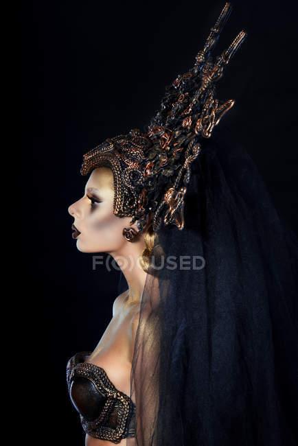 Вид збоку жінка з фантазія макіяж у великих корони — стокове фото