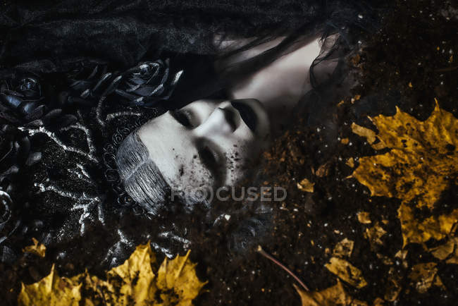 Portrait of woman with fantasy makeup lying on ground with autumn leaves — Stock Photo