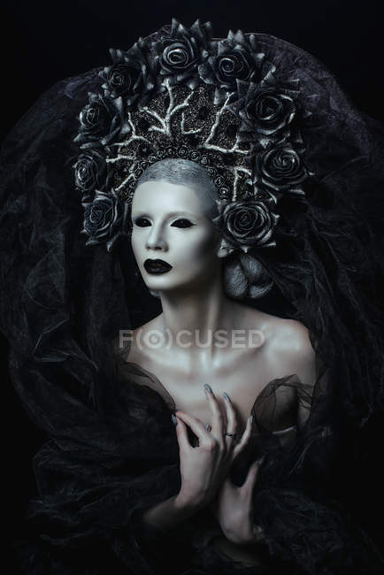 Portrait of woman with fantasy makeup wearing large crown — Stock Photo