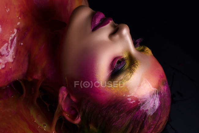 Profile of woman with fantasy makeup and paint on hair — Stock Photo