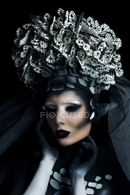 Woman with fantasy makeup wearing large crown and posing at camera — Stock Photo