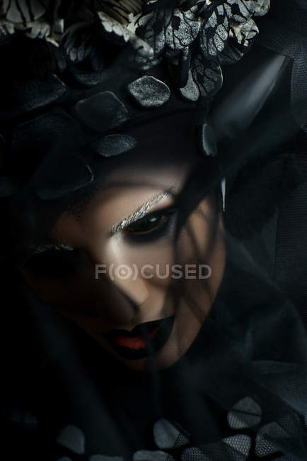 Woman with fantasy makeup in black eye lenses looking at camera — Stock Photo