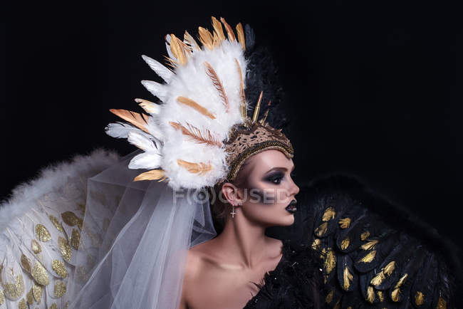 Woman with fashion makeup wearing feathers crown — Stock Photo
