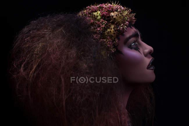 Vista lateral da mulher com maquiagem fantasia e penteado — Fotografia de Stock