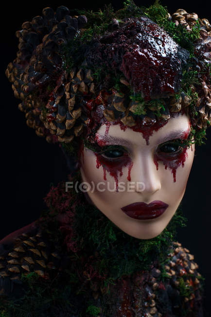 Woman with bloody makeup wearing fantasy clothes and crown — Stock Photo