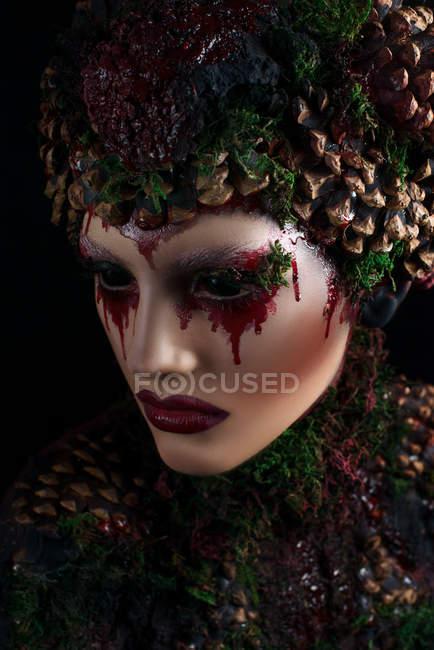Женщина с окровавленным макияжем в фантазийной одежде и короне — стоковое фото