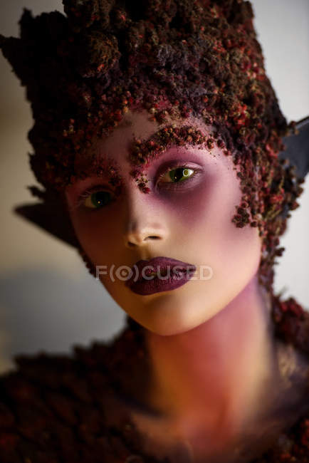 Portrait of young woman with fantasy makeup art and floral decorations — Stock Photo