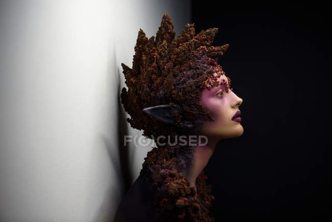 Side view of young woman with fantasy makeup art and floral decorations — Stock Photo