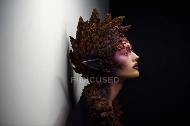 Вид сбоку молодой женщины с фантазии искусства макияж и цветочные украшения — стоковое фото