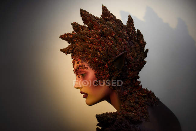 Profile of young woman with fantasy makeup art and floral decorations — Stock Photo