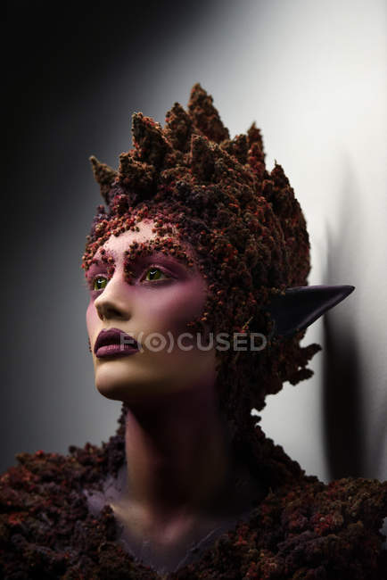Young woman with fantasy makeup art and floral decorations looking away — Stock Photo