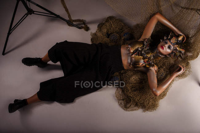 Female monster with headdress and clothes made from fishes laying on ground with net — Stock Photo