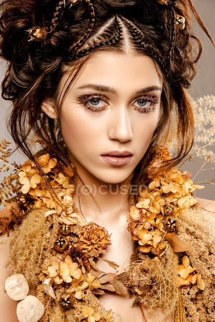 Attraente donna alla moda con trucco dorato e ghirlanda guardando la fotocamera — Foto stock