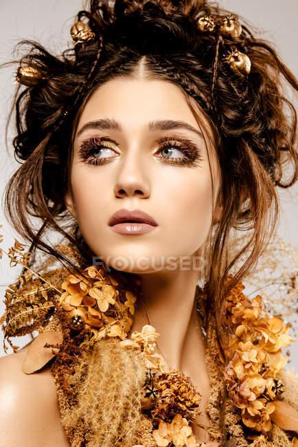 Mulher elegante atraente com maquiagem dourada e coroa olhando para longe — Fotografia de Stock