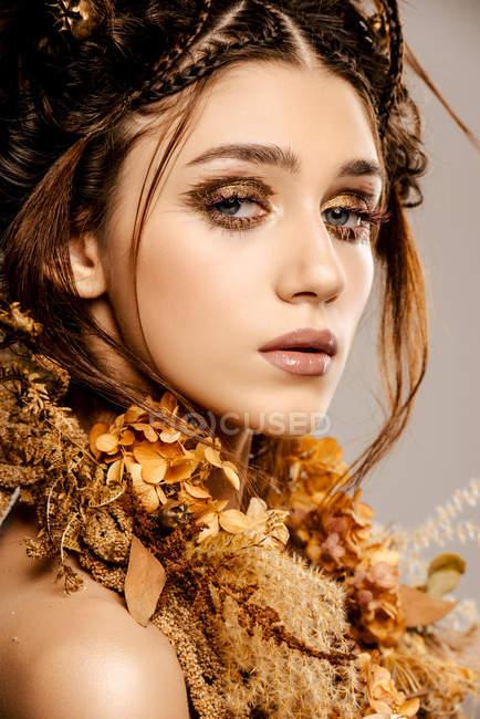 Mulher elegante atraente com maquiagem dourada e grinalda olhando para a câmera — Fotografia de Stock