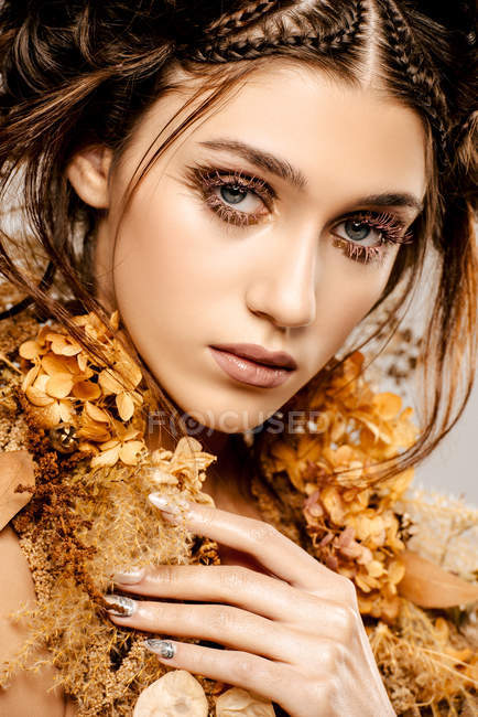 Attraktive modische Frau mit goldenem Make-up und Kranz blickt in die Kamera — Stockfoto