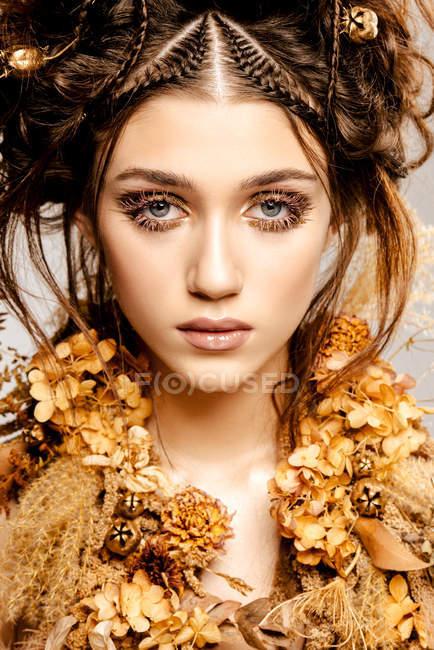 Приваблива модна жінка з золотим косметиком і вінком, що дивиться на камеру. — стокове фото
